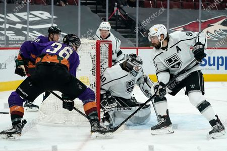 Los Angeles Kings defenseman Drew Doughty (8) helps out Kings goaltender Calvin Petersen (40) as Arizona Coyotes right wing Christian Fischer (36) attempts a shot during the first period of an NHL hockey game, in Glendale, Ariz