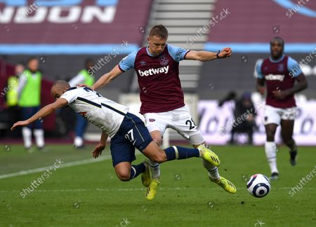 West Ham's Tomas Soucek, centre, duels for the ball with Tottenham's Lucas Moura during the English Premier League soccer match between West Ham United and Tottenham at the London Stadium in London