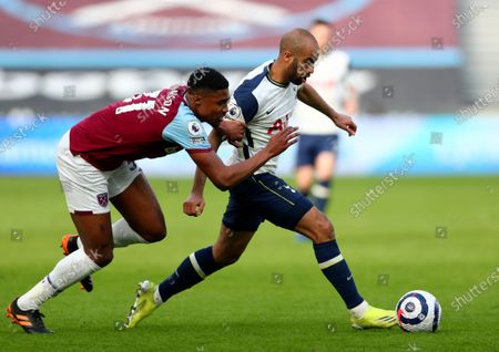 Tottenham's Lucas Moura, right, duels for the ball with West Ham's Ben Johnson during the English Premier League soccer match between West Ham United and Tottenham at the London Stadium in London