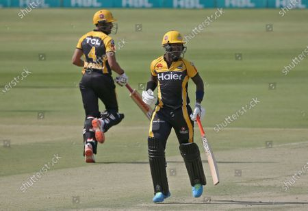 Peshawar Zalmi's Sherfane Rutherford, right and Ravi Bopara run between the wickets during a Pakistan Super League T20 cricket match between Peshawar Zalmi and Lahore Qalandars at the National Stadium, in Karachi, Pakistan