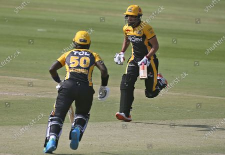 Peshawar Zalmi's Ravi Bopara, right, and Sherfane Rutherford run between the wickets during a Pakistan Super League T20 cricket match between Peshawar Zalmi and Lahore Qalandars at the National Stadium, in Karachi, Pakistan