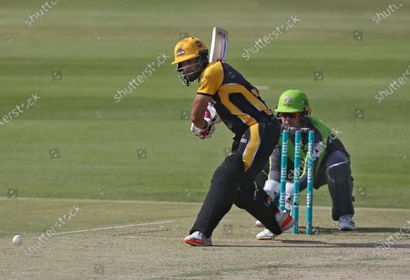 Stock Photo of Peshawar Zalmi Ravi Bopara, left, plays a shot while Lahore Qalandars wicketkeeper Ben Dunk watches during a Pakistan Super League T20 cricket match between Peshawar Zalmi and Lahore Qalandars at the National Stadium, in Karachi, Pakistan