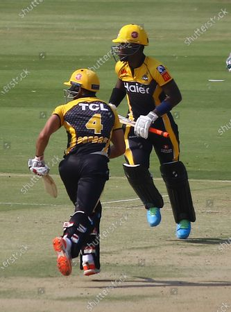 Peshawar Zalmi's Sherfane Rutherfordv (R) Ravi Bopara (L) run between the wickets during the Pakistan Super League (PSL) T20 cricket match between the Lahore Qalandars and Peshawar Zalmi at the National Stadium in Karachi, Pakistan, 21 February 2021.