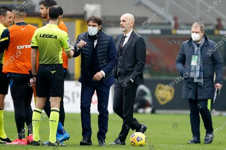 Inter Milan's head coach Antonio Conte, 3rd from right, and AC Milan's manager Stefano Pioli, 2nd from right, walks off the pitch after the Serie A soccer match between AC Milan and Inter Milan, at the Milan San Siro Stadium, Italy, . Inter won 3-0