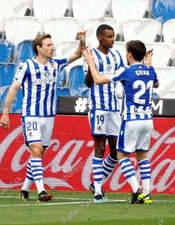Real Sociedad's striker Alexander Isak (C) celebrates with teammates Nacho Monreal (L) and David Silva (R) after scoring the 1-0 lead during the Spanish LaLiga soccer match between Real Sociedad and Deportivo Alaves held at Reale Arena stadium in San Sebastian, northern Spain, 21 February 2021.