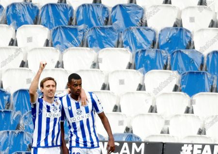 Real Sociedad's striker Alexander Isak (R) celebrates with teammate Nacho Monreal (L) after scoring the 1-0 lead during the Spanish LaLiga soccer match between Real Sociedad and Deportivo Alaves held at Reale Arena stadium in San Sebastian, northern Spain, 21 February 2021.