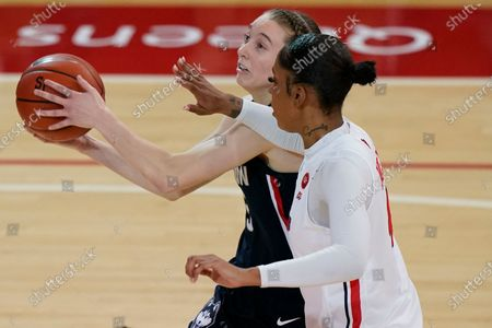 St. John's forward Raven Farley (4) defends Connecticut guard Paige Bueckers (5) during the second quarter of an NCAA college basketball game, at St. John's University in the Queens borough of New York