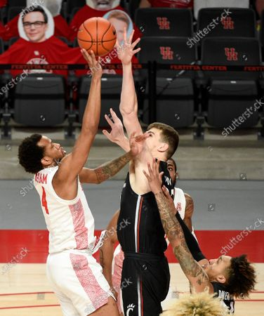 Houston forward Justin Gorham, left, shoots as Cincinnati center Chris Vogt, right, and guard Jeremiah Davenport, bottom right, defend during the first half of an NCAA college basketball game, in Houston