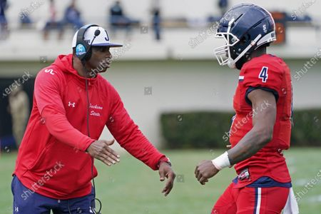 Jackson State football coach Deion Sanders, left, congratulates quarterback Jalon Jones (4) after guiding the team to a touchdown against Edward Waters during the first half of an NCAA college football in Jackson, Miss., . The game marked the head coaching debut of Sanders