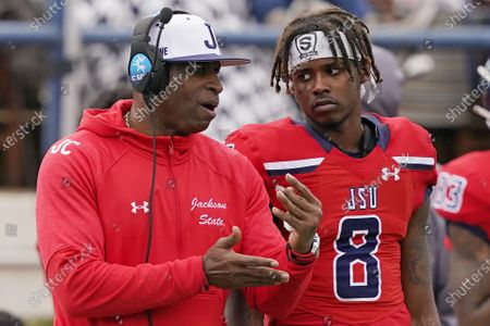 Jackson State football coach Deion Sanders, left, confers with quarterback Quincy Casey (8) during the second half of an NCAA college football game against Edward Waters in Jackson, Miss