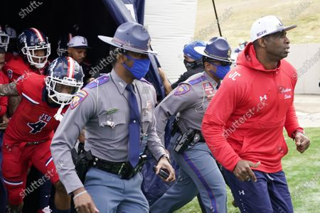 Jackson State football coach Deion Sanders, right, leads an accompanying security detail and his team onto the field prior to the first half of an NCAA college football game against Edward Waters in Jackson, Miss., . The game marks Sanders's collegiate head coaching debut
