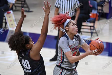 Mississippi forward Shakira Austin (0) goes up to shoot past Texas A&M center Ciera Johnson (40) during the second half of an NCAA college basketball game in Oxford, Miss
