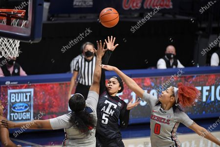 Texas A&M guard Jordan Nixon (5) shoots the ball past Mississippi forward Iyanla Kitchens (32) and forward Shakira Austin (0) during the first half of an NCAA college basketball game in Oxford, Miss