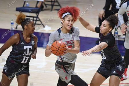 Mississippi forward Shakira Austin (0) drives the ball past Texas A&M guards Destiny Pitts (3) and Kayla Wells (11) during the second half of an NCAA college basketball game in Oxford, Miss., . Texas A&M won 66-55