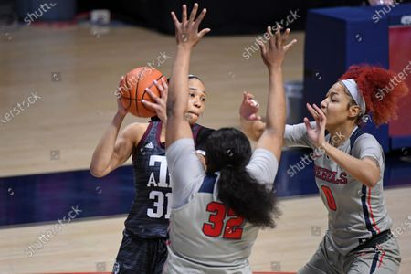 Texas A&M forward N'dea Jones (31) looks for room past Mississippi forwards Iyanla Kitchens (32) and Shakira Austin (0) during the first half of an NCAA college basketball game in Oxford, Miss