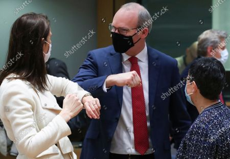 Belgium's Foreign Minister Sophie Wilmes, left, greets Ireland's Foreign Minister Simon Coveney, center, with an elbow bump during a meeting of EU foreign ministers at the European Council building in Brussels, . European Union foreign ministers on Monday will look at options for imposing fresh sanctions against Russia over the jailing of opposition leader Alexei Navalny as the 27-nation bloc considers the future of its troubled ties with the country