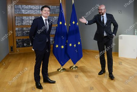 Ireland's Finance Minister and President of the Eurogroup Paschal Donohoe, left, is greeted by European Council President Charles Michel prior to a meeting at the European Council building in Brussels