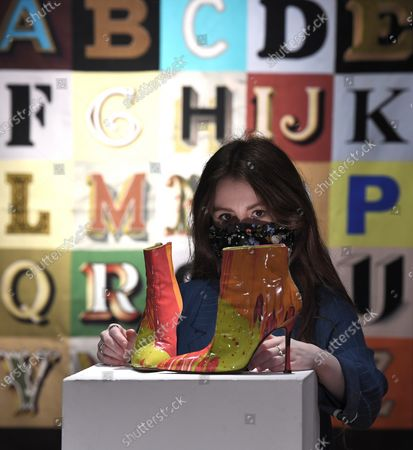 A Bonham's staff member with the SIR PETER BLAKE R.A. Alphabet, 2008 artwork, £ 8,000 - 12,000 and DAMIEN HIRST FOR MANOLO BLAHNIK Spin Boots, circa 2002£ 2,000 - 3,000 The sale takes place on 25 February in London.