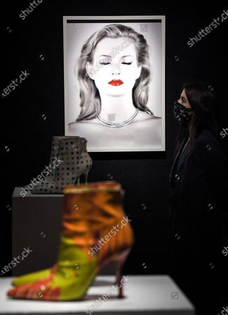 A Bonham's staff member with the Chris Levine (Canadian/British, born 1972), Kate Moss She's Light (Pure), artwork, 2014.  Estimate: £20,000 - 30,000 and the DAMIEN HIRST FOR MANOLO BLAHNIK Spin Boots, circa 2002£ 2,000 - 3,000. The sale takes place on 25 February in London.