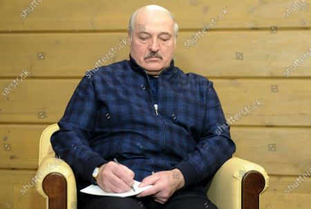 Belarusian President Alexander Lukashenko writes a note as he listens to Russian President Vladimir Putin during their meeting in the Black Sea resort of Sochi, Russia