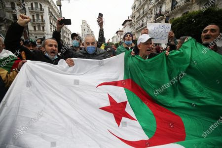 Algerians shout slogans as they march to mark the second anniversary of the popular protests in Algiers, Algeria, 22 February 2021. Algeria on 22 February 2021 celebrates the second anniversary of the mass protests movement, known as the Hirak which led to the resignation of the then president Abdelaziz Bouteflika. Current Algerian President Abdelmadjid Tebbounne announced on 18 February the pardon and release of about 60 people either sentenced or awaiting trial for charges related to participating in the Hirak protest movement. He also advised that he was dissolving the lower house of the Parliament which members had also been serving under the former president Bouteflika leading the way to early legislative elections later this year and a cabinet reshuffle.