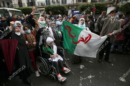 Algerians hold a national flag with Arabic inscription reading 'freedom' as they march to mark the second anniversary of the popular protests in Algiers, Algeria, 22 February 2021. Algeria on 22 February 2021 celebrates the second anniversary of the mass protests movement, known as the Hirak which led to the resignation of the then president Abdelaziz Bouteflika. Current Algerian President Abdelmadjid Tebbounne announced on 18 February the pardon and release of about 60 people either sentenced or awaiting trial for charges related to participating in the Hirak protest movement. He also advised that he was dissolving the lower house of the Parliament which members had also been serving under the former president Bouteflika leading the way to early legislative elections later this year and a cabinet reshuffle.