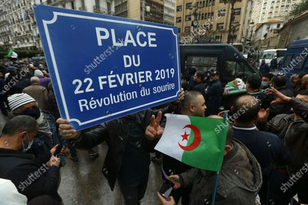 """Algerians demonstrate in Algiers, one with a plaque reading """"Square of Feb.22, 2019, the Smiling Revolution"""" to mark the second anniversary of the Hirak movement, . February 22 marks the second anniversary of Hirak, the popular movement that led to the fall of Algerian President Abdelaziz Bouteflika"""