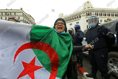 Woman holds an Algerian flag as Algerians demonstrate in Algiers to mark the second anniversary of the Hirak movement, . February 22 marks the second anniversary of Hirak, the popular movement that led to the fall of Algerian President Abdelaziz Bouteflika