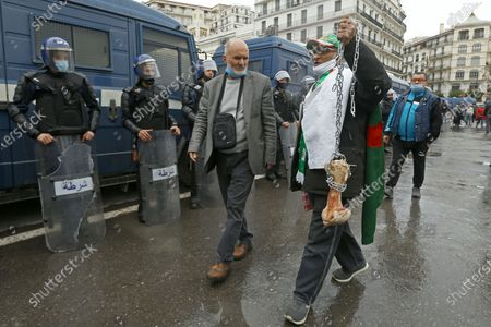 """Man holds a bone while shouting """"That's what's left for those who vote for the President"""" as Algerians demonstrate in Algiers to mark the second anniversary of the Hirak movement, . February 22 marks the second anniversary of Hirak, the popular movement that led to the fall of Algerian President Abdelaziz Bouteflika"""