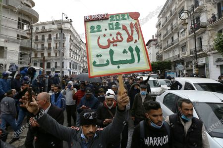 """Stock Picture of Algerians demonstrate, one with a poster reading """"Resistance Monday"""" in Algiers as they mark the second anniversary of the Hirak movement, . February 22 marks the second anniversary of Hirak, the popular movement that led to the fall of Algerian President Abdelaziz Bouteflika"""