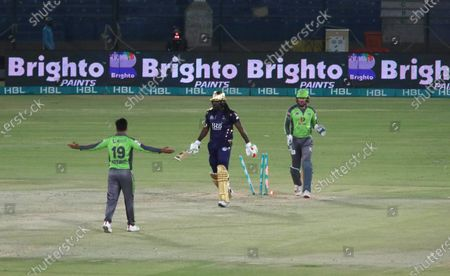 Stock Photo of Quetta Gladiator's Chris Gayle (C) is bowled out by Lahore Qalandars Rashid Khan (L) during the Pakistan Super League (PSL) T20 cricket match between the Lahore Qalandars and Quetta Gladiator's at the National Stadium in Karachi, Pakistan, 22 February 2021.