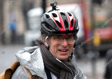 Robert Peston, Political editor of ITV news, arrives at Parliamnet by bicycle.