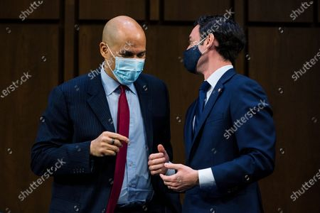 Sen. Cory Booker, D-N.J., and Sen. Jon Ossoff, D-Ga., talk during a break in Attorney General nominee Merrick Garland's confirmation hearing before the Senate Judiciary Committee, on Capitol Hill in Washington