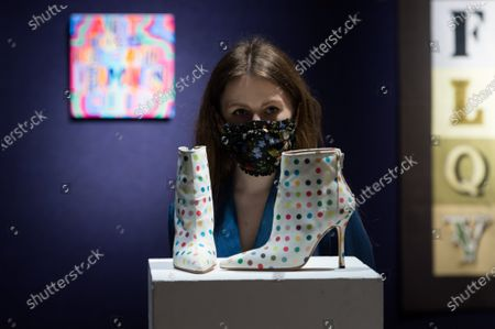 A gallery staff member poses with Damien Hirst X Manolo Blahnik Spot Boots, circa 2002, (est. £2,000-3,000) during a photo call for Bonhams' British. Cool. sale showcasing a diverse range of British and émigré talent from the last one hundred years, on February 22, 2021 in London, England. (Photo by WIktor Szymanowicz/NurPhoto)