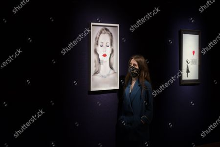 A gallery staff member stands between 'Kate Moss She's Light (Pure)', 2014, 3D print by Chris Levine (est. £20,000-30,000) donated by both Levine and Moss to raise funds for Oxfam GB and 'Girl with Balloon', 2004, by Banksy (est. £100,000-150,000) during a photo call for Bonhams' British. Cool. sale showcasing a diverse range of British and émigré talent from the last one hundred years, on February 22, 2021 in London, England. (Photo by WIktor Szymanowicz/NurPhoto)