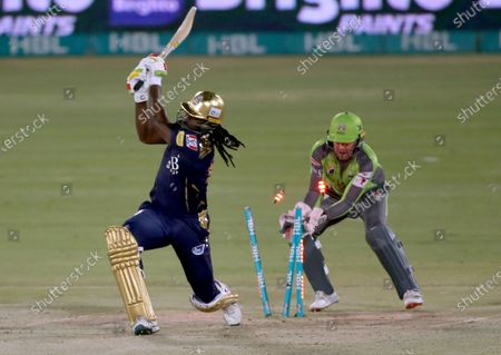 Stock Image of Quetta Gladiators' Chris Gayle, left, is bowled out by Lahore Qalandars' Rashid Khan while teammate Ben Dunk watches during a Pakistan Super League T20 cricket match between Lahore Qalandars and Quetta Gladiators at the National Stadium, in Karachi, Pakistan