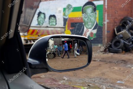 Portrait of former Zimbabwean President Robert Mugabe is seen in the background as a push cart operator transports a load of goods in Harare, . Zimbabweans commemorated National Youth Day, a day set aside as a public holiday by the former leader who died in 2019