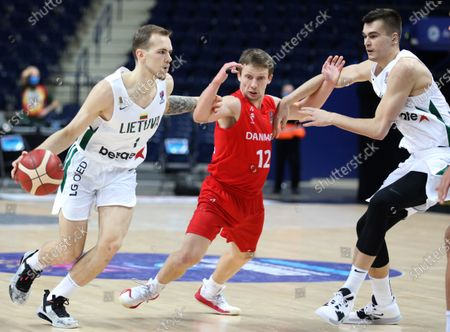 Denmark's Frederik Nielsen, center, and Lithuania's Arnas Velicka, left, and Lithuania's Gytis Masiulis, right, challenge for the ball during the FIBA EuroBasket 2022 Group C qualifying basketball match between Denmark and Lithuania at Avia Soliutions Group arena in Vilnius, Lithuania