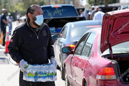 Rep. Al Green, D-Texas, hands out cases of water at a food and water distribution site, in Houston. The city's boil water notice has been rescinded however many residents lack water at home due to broken pipes