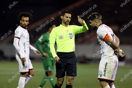 Saudi referee Majed Al Shamrani (C) speaks with Al-Shabab's player Ever Banega (R) during the Saudi Professional League soccer match between Al-Shabab and Al-Ahli at Prince Khalid bin Sultan Stadium, in Riyadh, Saudi Arabia, 22 February 2021.
