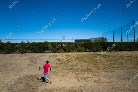Kenny Smith, 39, chases a ball that went over the fence during the Chicago Cubs' spring training baseball workout in Mesa, Ariz