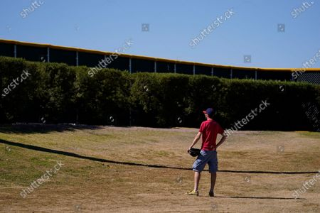 Stock Photo of Kenny Smith, 39, stands outside the Chicago Cubs' practice field in hopes to catch a ball during the team's spring training baseball workout in Mesa, Ariz