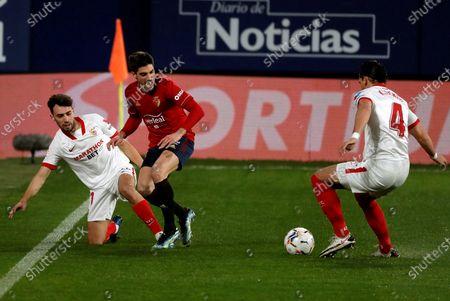 Osasuna's Nacho Vidal (C) in action against Sevilla FC's Karim Jekik (R) and Munir el Haddadi (L) during a Spanish LaLiga soccer match between Osasuna and Sevilla FC at El Sadar stadium in Pamplona, Navarra, northern Spain, 22 February 2021.