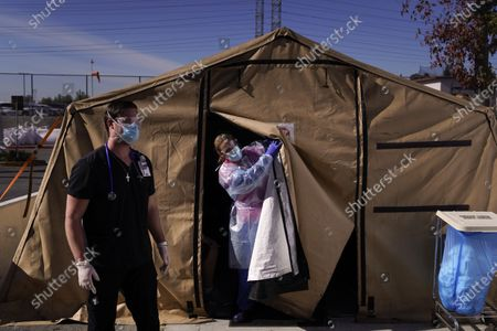 Stock Image of Registered nurse Keith Robinson, right, watches as fellow nurse Angela Coomds calls out a patient's name from a COVID-19 triage tent at Providence Holy Cross Medical Center in the Mission Hills section of Los Angeles. The U.S. death toll from COVID-19 has topped 500,000 - a number so staggering that a top health researchers says it is hard to imagine an American who hasn't lost a relative or doesn't know someone who died