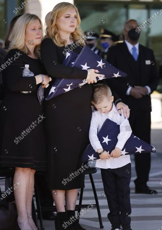Nole Bergenske Penton, center, and her son Cashton grip folded U.S. flags given them by Dallas Police Chief Eddie Garcia following a funeral service for her husband Dallas Police officer Mitchell Penton at Prestonwood Baptist Church in Plano, Texas, . Penton was killed, Saturday, Feb. 13, 2021, in a crash involving a drunk driving suspect