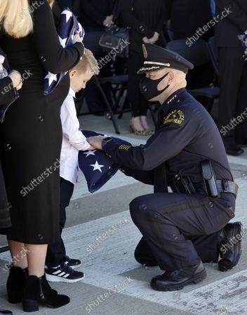 Dallas Police Chief Eddie Garcia (right) hands a folded U.S. flag to Dallas Police officer Mitchell Penton's son Cashton following a funeral service for his dad at Prestonwood Baptist Church in Plano, Texas, . Penton was killed, Saturday, Feb. 13, 2021, in a crash involving a drunk driving suspect