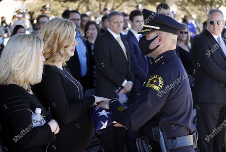 Stock Image of Dallas Police Chief Eddie Garcia (right) hands Nole Bergenske Penton (center) a folded U.S. flag given to her and her family following a funeral service for her husband Dallas Police officer Mitchell Penton at Prestonwood Baptist Church in Plano, Texas, . Penton was killed, Saturday, Feb. 13, 2021, in a crash involving a drunk driving suspect