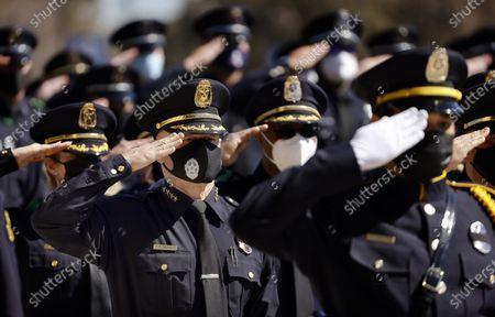 Dallas Police Chief Eddie Garcia (left) salutes alongside his comrades during a funeral service for Dallas Police officer Mitchell Penton at Prestonwood Baptist Church in Plano, . Penton was killed Saturday, Feb. 13, 2021, in a crash involving a drunk driving suspect