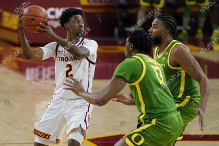 Oregon forward Chandler Lawson (13) and guard LJ Figueroa, right, defend against Southern California guard Tahj Eaddy (2) during the second half of an NCAA college basketball game, in Los Angeles
