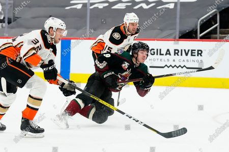 Stock Photo of Arizona Coyotes right wing Clayton Keller (9) shoots on goal in between Anaheim Ducks defenseman Jacob Larsson (32) and center Ryan Getzlaf (15) in the second period during an NHL hockey game, in Glendale, Ariz
